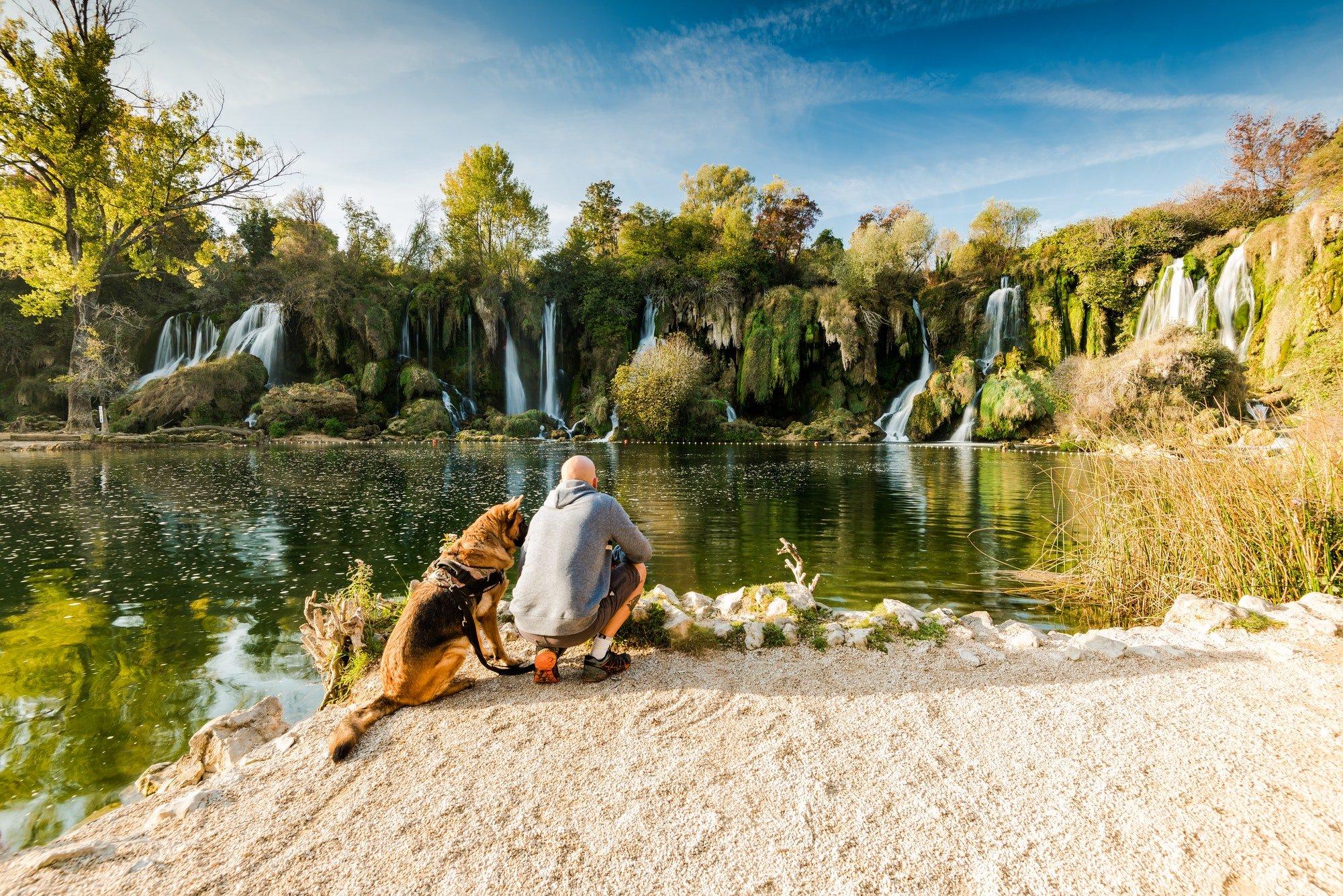 Active man sitting with dog at Kravica waterfall,Bosnia